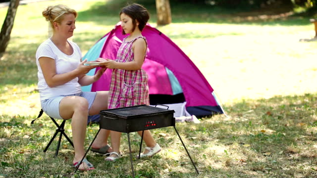 Young Mother And Daughter Grilling Meat On Barbecue video