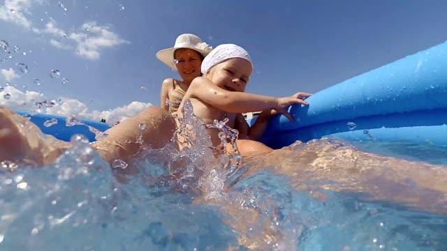 vídeos de stock, filmes e b-roll de jovem mãe e filha tendo diversão na piscina - inflável
