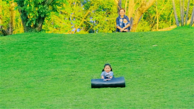 Young Mother And daughter having fun sliding down a grassy hill at Mae Moh Lampang, Thailand video
