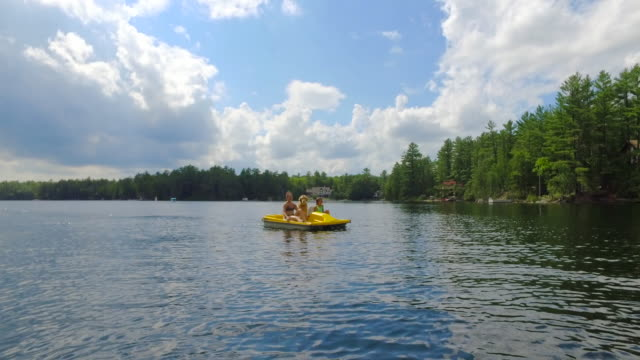 Young mother and daughter on a paddle boat with their dog video