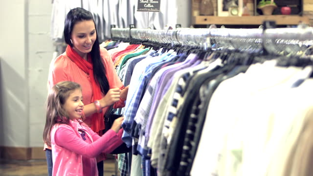 stockvideo's en b-roll-footage met jonge moeder en dochter winkelen in kledingwinkel - discountwinkel