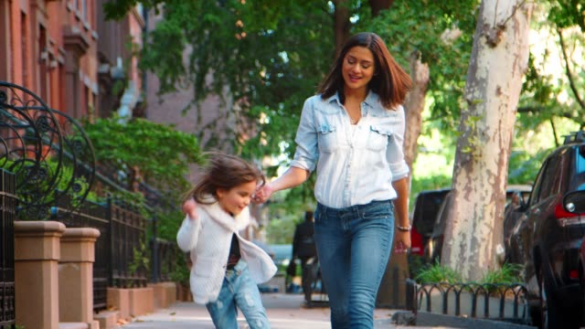 young mother and daughter walking in the street, front view - marciapiede video stock e b–roll