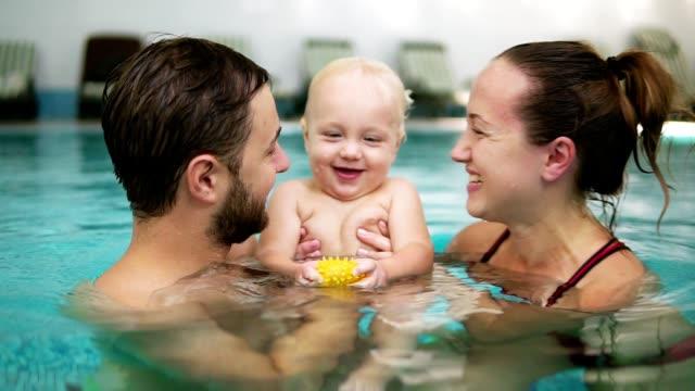 stockvideo's en b-roll-footage met jonge moeder en vader zijn houden hun schattig kind in het zwembad en kussen elkaar in hun lippen. gelukkig kind lacht - swimmingpool kids