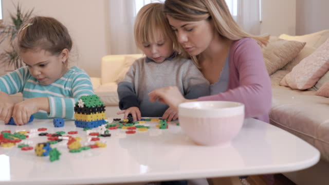 young mother and her children playing with puzzles in the living room. - puzzle video stock e b–roll