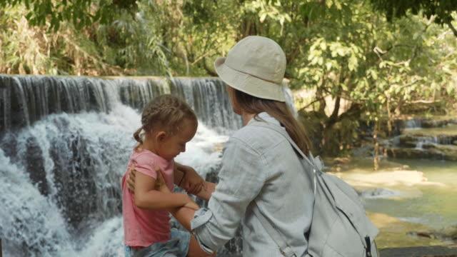 若い母親と滝のカスケードに休んでかわいい娘 ビデオ