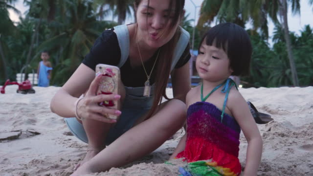 vídeos de stock e filmes b-roll de young mother and her daughter taking selfie with smart phone on the beach - fotografar