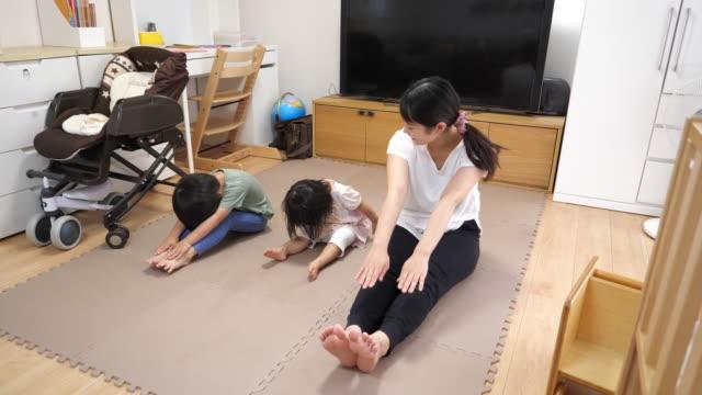 vídeos de stock e filmes b-roll de young mother and her kids exercising in living room - treino em casa