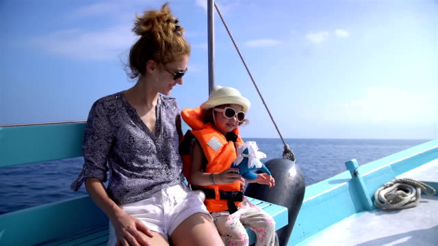 Young mother and her little daughter are sailing on a sea boat. Slow motion. video