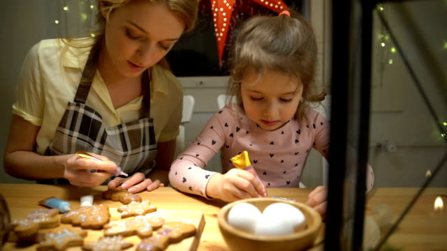 vídeos de stock e filmes b-roll de young mother and her little daughter prepare christmas cookies - christmas cookies