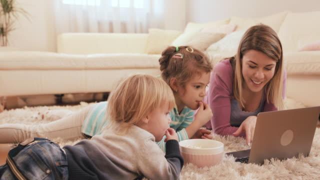 若い母親と彼女の 2 人の子供がカーペットの上にリラックスして、ラップトップ上で何かを見てします。 ビデオ