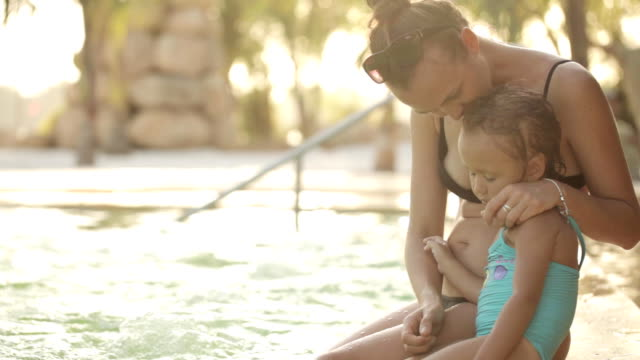 Young mother and little cute daughter sits and hugs on poolside at sunset video