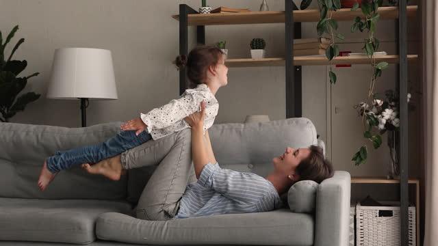 Young mother and little daughter play together at home