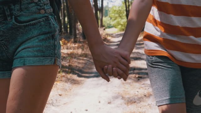 young mother and son holding hands walking along a path in forest. slow motion - pantaloncini video stock e b–roll