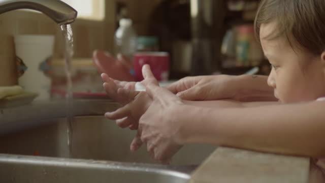 ung mamma och son handtvätt i diskbänk - washing hands bildbanksvideor och videomaterial från bakom kulisserna