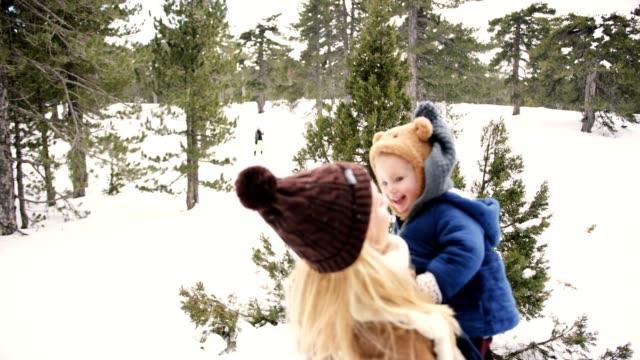 雪の中で楽しく若い母親と幼児の娘 ビデオ