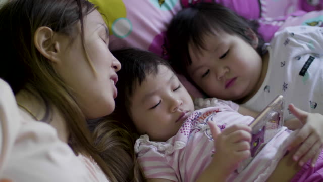 Young Mother And Two Daughters Watching A Movie On Smart Phone video