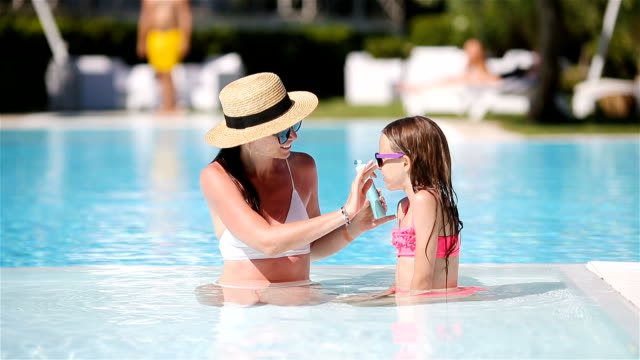 Video Young mother applying sun cream to daughter nose