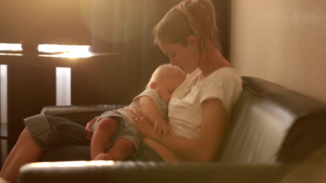 vídeos de stock e filmes b-roll de young mother, breastfeeding on sunset on quiet evening her little baby boy in sunny living room - amamentação