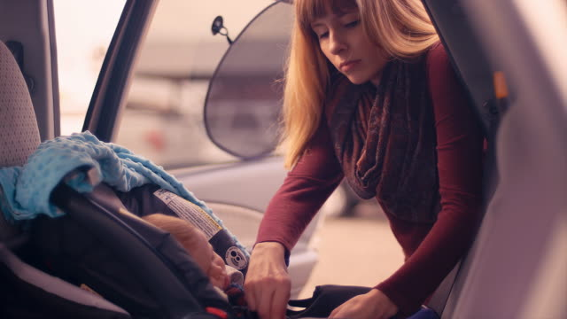 A young mother buckling her baby daughter into her car seat