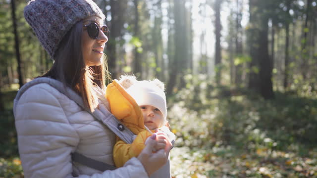 Young mother carrying her baby in baby carrier and walking through forest on sunny day