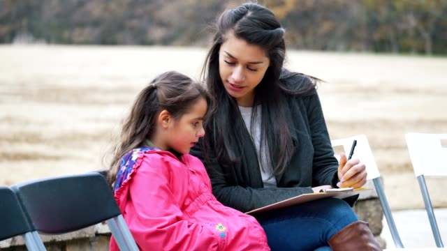 Young mother completes new patient paperwork for sick daughter While visiting a free outdoor health clinic, a young mom completes patient forms for her young daughter. The woman smiles while talking with her daughter while filling out the forms. clipboard stock videos & royalty-free footage
