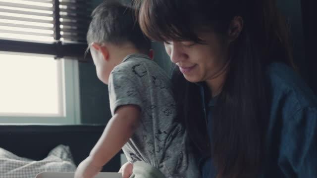 若い母親は、男の子の赤ちゃんをドレスアップ ビデオ