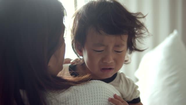 vídeos y material grabado en eventos de stock de joven madre abrazando niño llorando - llorar