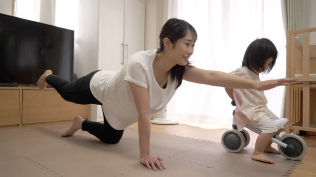 Young mother exercising at home, daughter riding tricycle