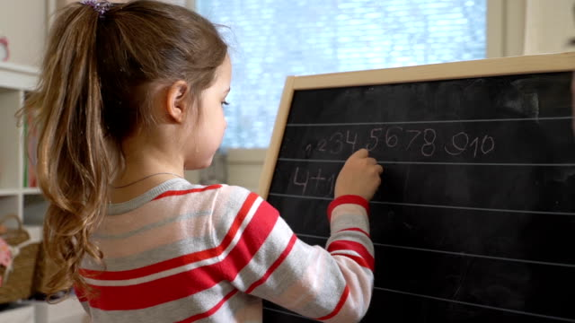 Young mother explaining arithmetic to cute little daughter at home video
