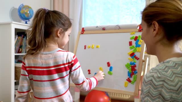 junge mutter erklären, arithmetik, niedliche kleine tochter zu hause - matheunterricht stock-videos und b-roll-filmmaterial