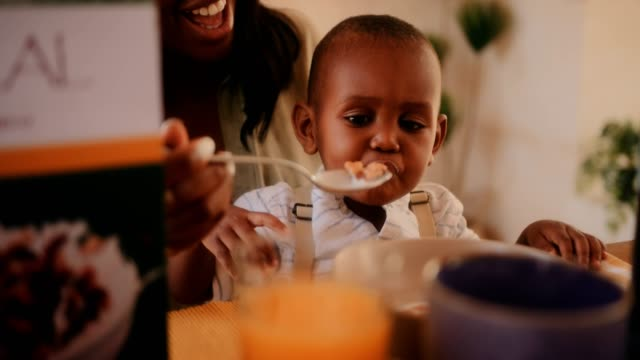 Young mother feeding little baby son cereal in the morning Happy young mother feeding hungry little son cereal with milk during breakfast in the morning feeding stock videos & royalty-free footage
