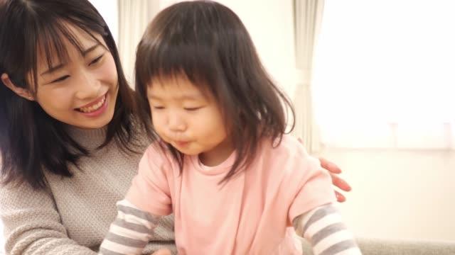 幼い母親が小さな娘にブドウを与える - 母娘 笑顔 日本人点の映像素材/bロール