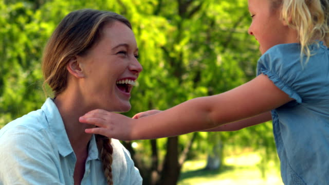 Young mother giving her daughter a hug in the park video