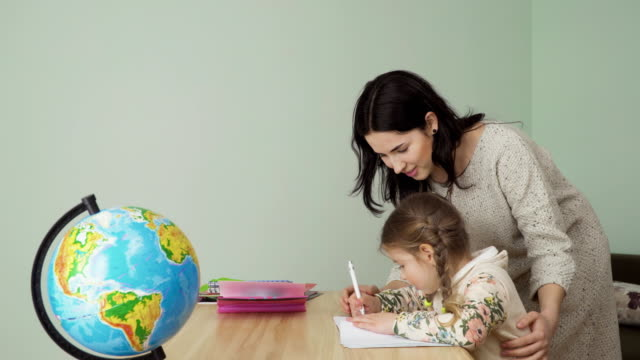 Young mother help her little daughter to make homework video