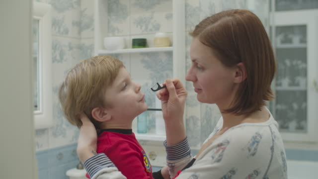 Young mother helps preschool boy in red pajamas with brushing teeth with dental floss. Fun family bath routine. Mother and son laughing in bathroom.