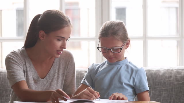 Young mother helps with school task to little daughter