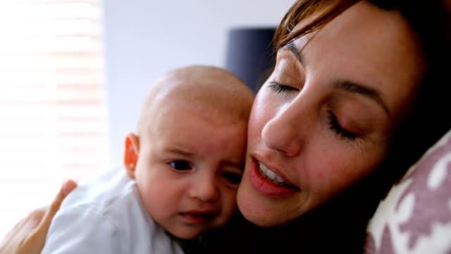 junge mutter halten und küssen ihr baby mit nach hause 4k - alleinerzieherin stock-videos und b-roll-filmmaterial