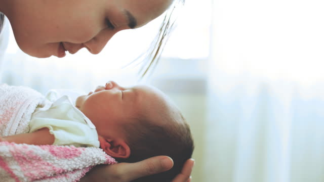 young mother holding and kissing her newborn baby - parenting video stock e b–roll