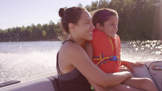Young mother holding her daughter while enjoying a boat ride video