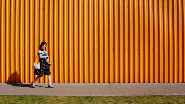 Jeune maman dans une robe noir et blanc, portant un petit garçon le long du mur jaune à l'extérieur par une journée ensoleillée - Vidéo