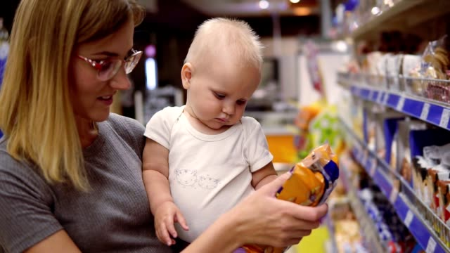 Young mother in glasses holding her child in her arms while choosing cookies on the shelves in the supermarket. Thoughtful mom looking at the product content, carefully choosing products for her child Young mother in glasses holding her child in her arms while choosing cookies on the shelves in the supermarket. Thoughtful mom looking at the product content, carefully choosing products for her child. snack aisle stock videos & royalty-free footage