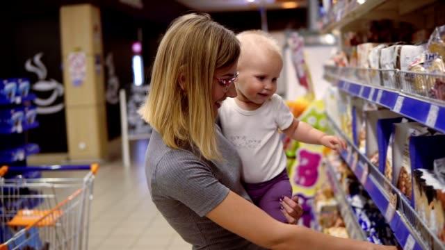 vídeos y material grabado en eventos de stock de joven madre en vasos con su hijo en sus brazos mientras selecciona cookies en los anaqueles en el supermercado. mamá pensativa mirando el contenido del producto, elegir cuidadosamente los productos para su hijo - snack aisle