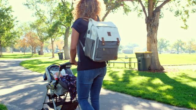vídeos de stock e filmes b-roll de young mother in the park - mochila saco