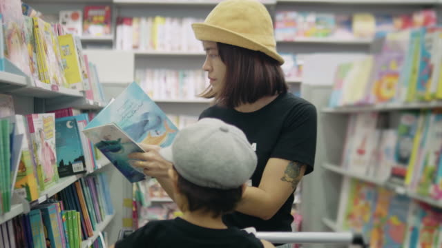 Young mother is choosing a book with her son.