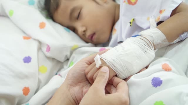 Young mother is holding hand bandaged of sick daughter while she is sleeping on bed with love and care in the hospital in slow motion shot video