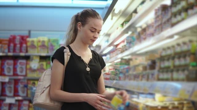 junge mutter liest inschriften auf einem etikett in ein glas mit baby püree im shop - etikett stock-videos und b-roll-filmmaterial