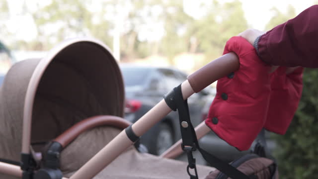 A young mother on a walk with a newborn baby during a cool period. Family and motherhood concept. video