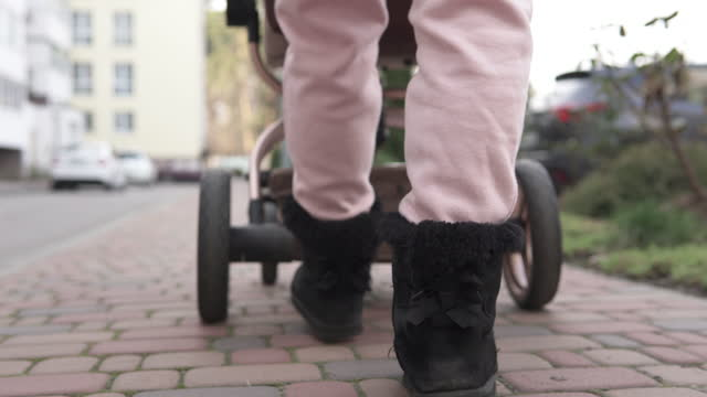 A young mother on a walk with a newborn baby during a cool period. Family and motherhood concept. Close-up of legs with a baby stroller. video