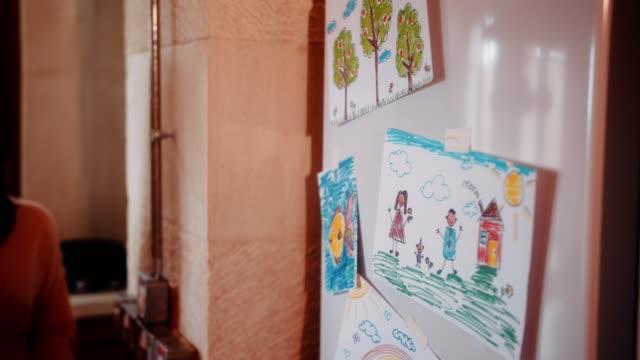 giovane madre che apre la porta del frigorifero con disegni per bambini in cucina - fumetto creazione artistica video stock e b–roll