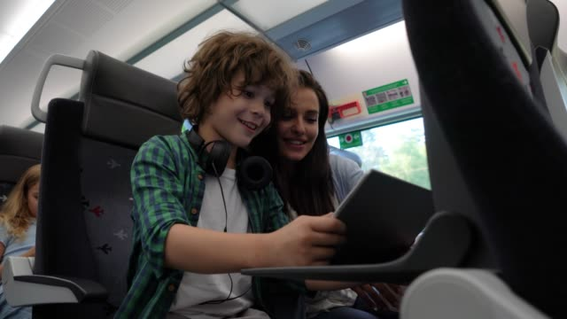 Young mother playing with her son using a tablet talking and laughing while commuting on train